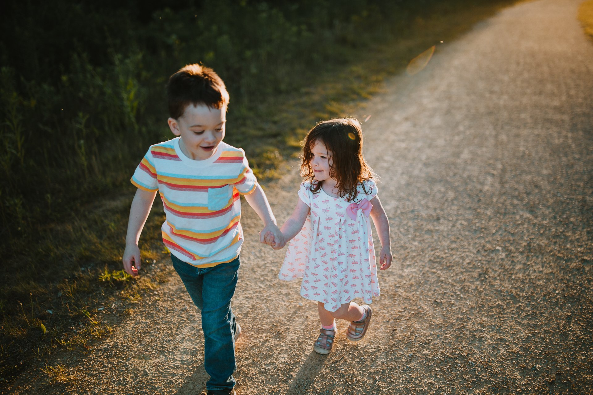 A young brother and sister walk down a gravel path hand in hand.