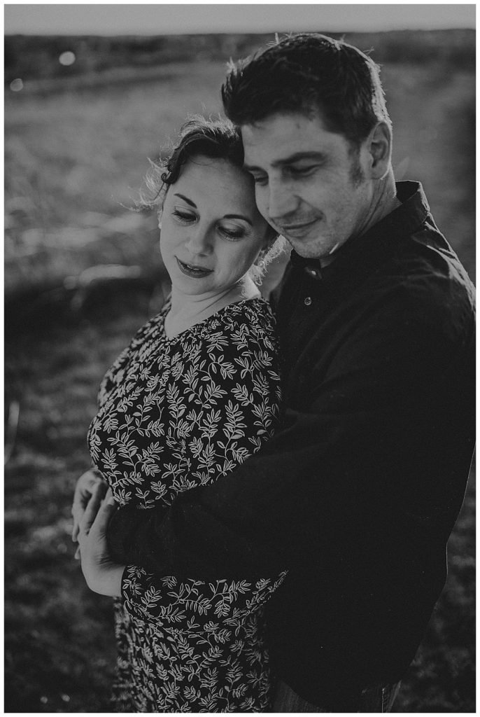 A man and woman embrace in a field. The image is in black and white.